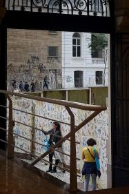Do lado de fora do Centro Cultural Correios, a fã faz uma selfie mostrando os cartazes colados nos tapumes.